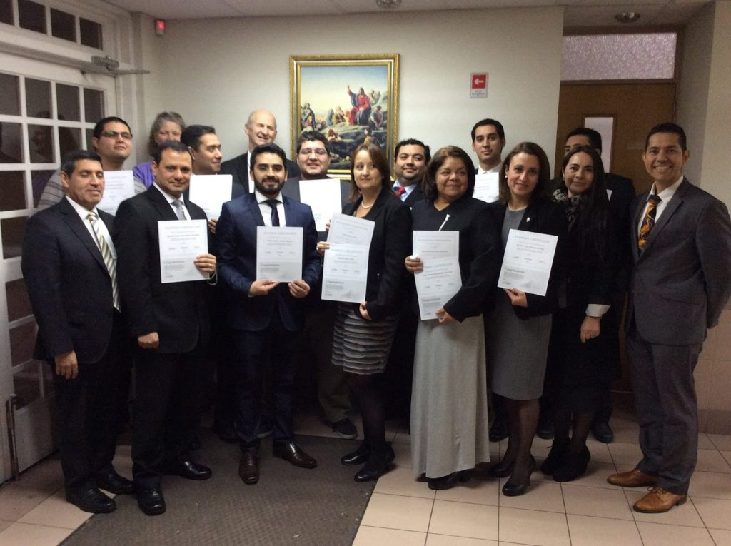 Ismar (right) stands with a group of Chilean Pathway graduates, Elder and Sister Checkett of Santiago, (behind) and Elder Patricio M. Giuffra (left).