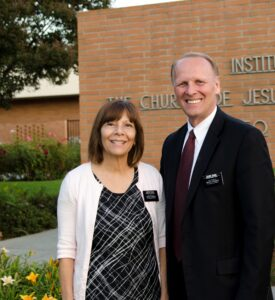 two senior missionaries standing in front of a meeting house