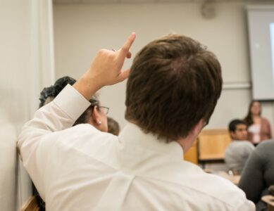 student raising his hand in a classroom